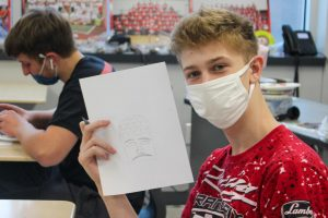 Students draw sketches before sculpting clay figures in history class.