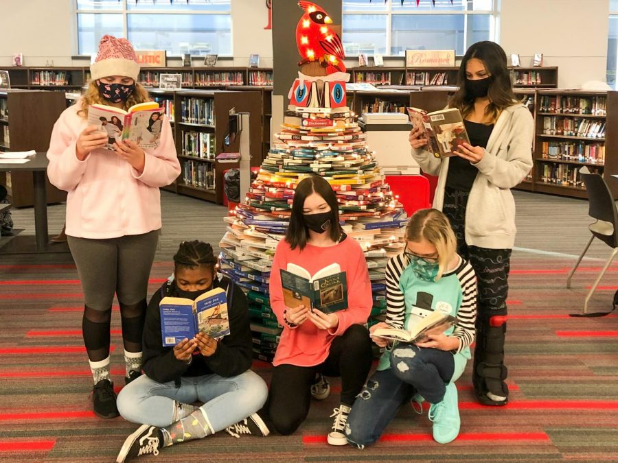 """""""Reading Around the Book Tree."""" Several students gather in the library around the creative Cardinal book tree to enjoy their texts."""